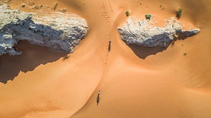 Aerial view of two persons walking in the desert of Sharjah.