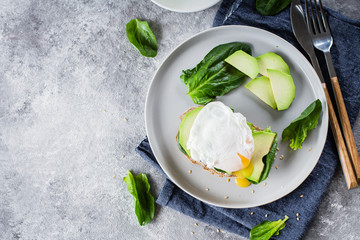 Sandwich with avocado, spinach and poached egg on whole wheat bread on plate on stone background. Helathy Food Breakfast Concept. Top view, copy space