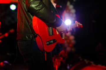 Closeup photo of bass guitar player hands, soft selective focus, bright live music theme