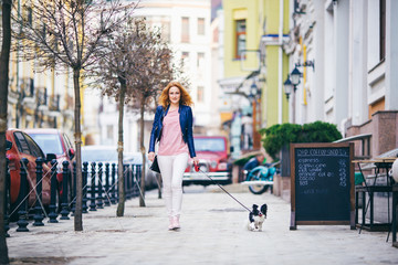 young redhaired Caucasian woman walking along European street with small Chihuahua breed dog of two colors on leash. Cloudy, warm autumn spring weather. Girl Dressed in leather jacket and pink shoes