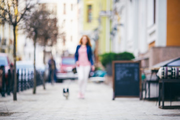Blurred background A young red-haired Caucasian woman is walking along a European street with a small Chihuahua breed dog of two colors on a leash. Girl Dressed in a leather jacket and pink shoes
