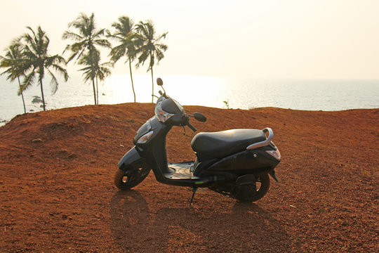 Black scooter stands on top of the mountain against the background of the sea and palms, India, GOA