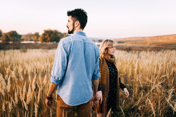 handsome guy with a beard in a blue denim shirt gentle hugs, hand holding and kissing a girl with blond hair in a blue dress and yellow scarf in a field at sunset. stylish couple