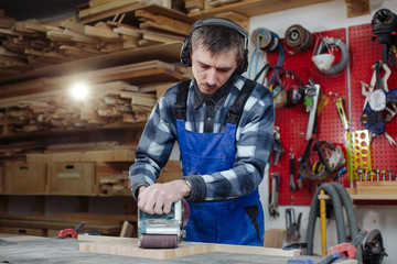 worker grinds a board in a woodworking workshop on an old workbench
