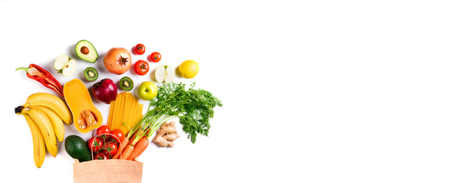 Healthy food background. Healthy vegetarian food in paper bag pasta, vegetables and fruits on white. Shopping food concept. Long format with copy space