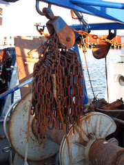 Laesoe / Denmark: Rusty fishing gear chains on a fishing trawler at the quayside in Oesterby Havn