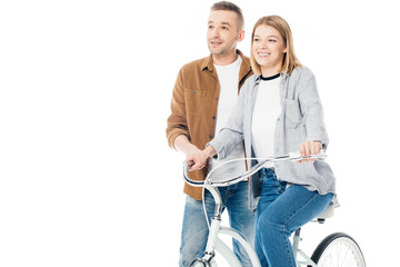 smiling man and wife on bicycle looking away isolated on white