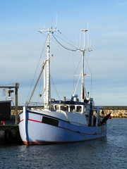 Laesoe / Denmark: Fishing trawler at the quayside in Oesterby Havn on a sunny day in December