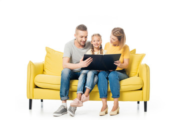parents looking at photos in photo album while sitting on yellow sofa together with daughter isolated on white