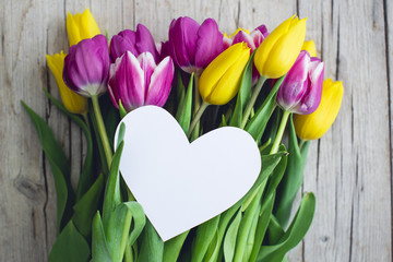 Greeting card - Pink and yellow tulips on a wooden background
