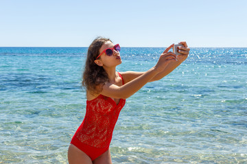 young girl having fun taking smartphone selfie pictures of herself. travel holidays