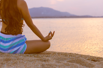 young woman sitting meditation and practicing yoga on  beach as sunlight in morning