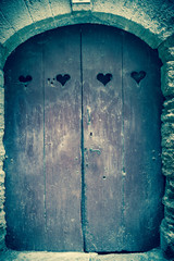 Old wooden door with four carved hearts. Provence, France. Vintage Valentines day background. Toned blue photo/