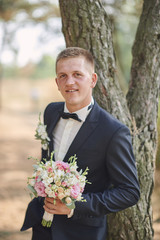 Handsome groom at wedding tuxedo smiling and waiting for bride. Happy smiling groom newlywed.