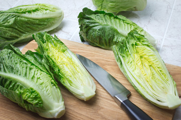 Romaine lettuce on kitchen board with knife