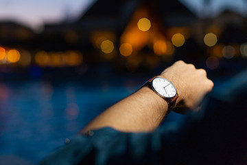A man at a fancy resort checks his watch at nighttime and thinks about the end of his vacation