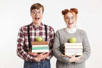Happy couple of school nerds holding stack of books
