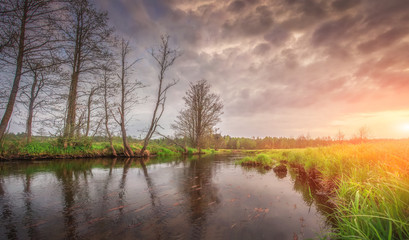 Spring landscape of river with picturesque grass and trees on her shore at bright sunrise in the morning. Cloudy sky over beautiful river and natural nature around. Rural scene. Sunshine on horizon.