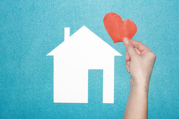 concept of love in family and at home. hand holds red heart over white paper house on blue background. Insurance of real estate. Loving and protecting the house.