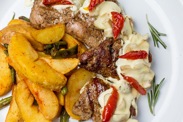 Baked chicken meat. With fried potatoes, pesto sauce and vegetables. In a round plate. View from above. Close-up