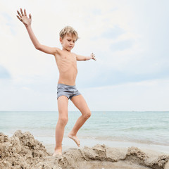 Portrait of healthy little boy playing on the seashore with sand, image with square aspect ratio