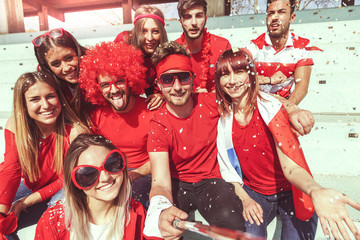 group of fans dressed in red color takes a selfie in the stand
