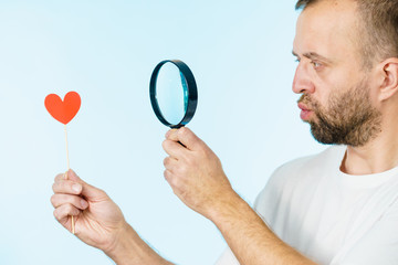 Uncertain man looking at love heart