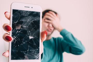 Broken glass screen smartphone in hand of upset girl, white background