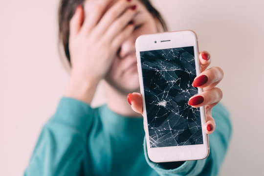 Broken glass screen smartphone in hand of upset girl, white background