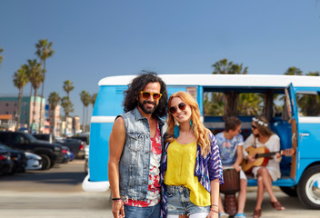 summer holidays, road trip, travel and vacation concept - smiling young hippie couple with friends over minivan car and venice beach in los angeles background