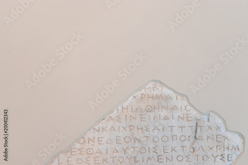 Ancient greek words carved into stone with cracked  For