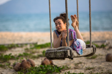 Young mixed race woman on the wooden swings on sea beach.