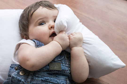 Little baby playing with pillow