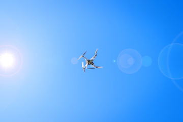 Drone flying in sunshine on blue sky background