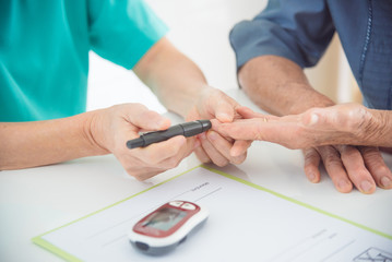 Close up of nurse hands using lancet to checking patient blood sugar level by Glucose meter ,diabetes concept