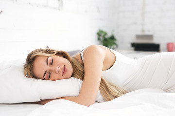Pretty, sleeping young woman lying in the bed.