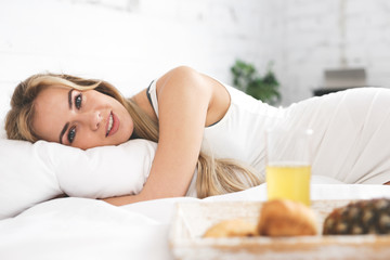 Morning breakfast. Portrait of happy young woman lying in the bed.Looking at the camera.