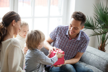 Little son presenting gift for dad, cute boy holding box making daddy surprise present, kids congratulating excited happy parent with birthday, young family celebrating fathers day together concept