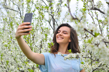 Girl make a selfie in blooming orchard. Beautiful woman enjoy in nature in spring