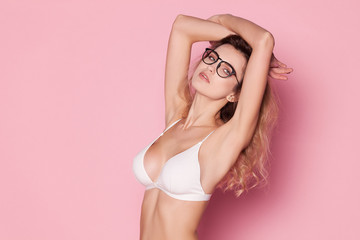 Beautiful woman in white lingerie on a pink background with glass