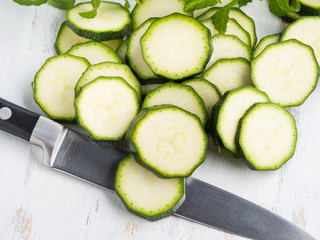 Cutting fresh zucchini on wooden board. Cooking vegetables