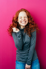 Funny young redhead woman with a cheesy grin