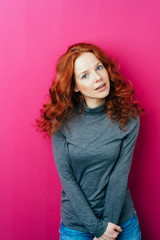 Young red-haired woman against pink background