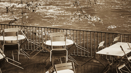 Riverside cafe after closure in Provence. After rain. Tables and chairs with rain drops. Sepia...