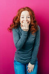 Young red-haired laughing woman on pink background