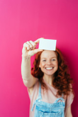 Young cheerful woman holding blank white card