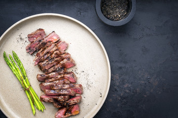 Traditional barbecue skirt steak sliced with green asparagus and smoked pepper as close-up on a plate