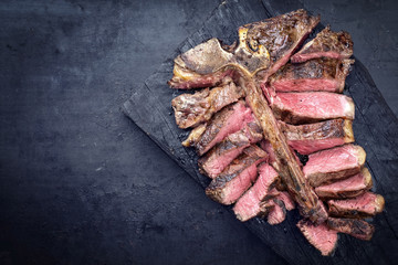 Barbecue dry aged wagyu porterhouse steak sliced as top view on a burnt board with copy space left
