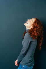 Young red-haired cheerful woman laughing