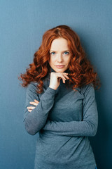 Young red-haired serious woman against blue wall
